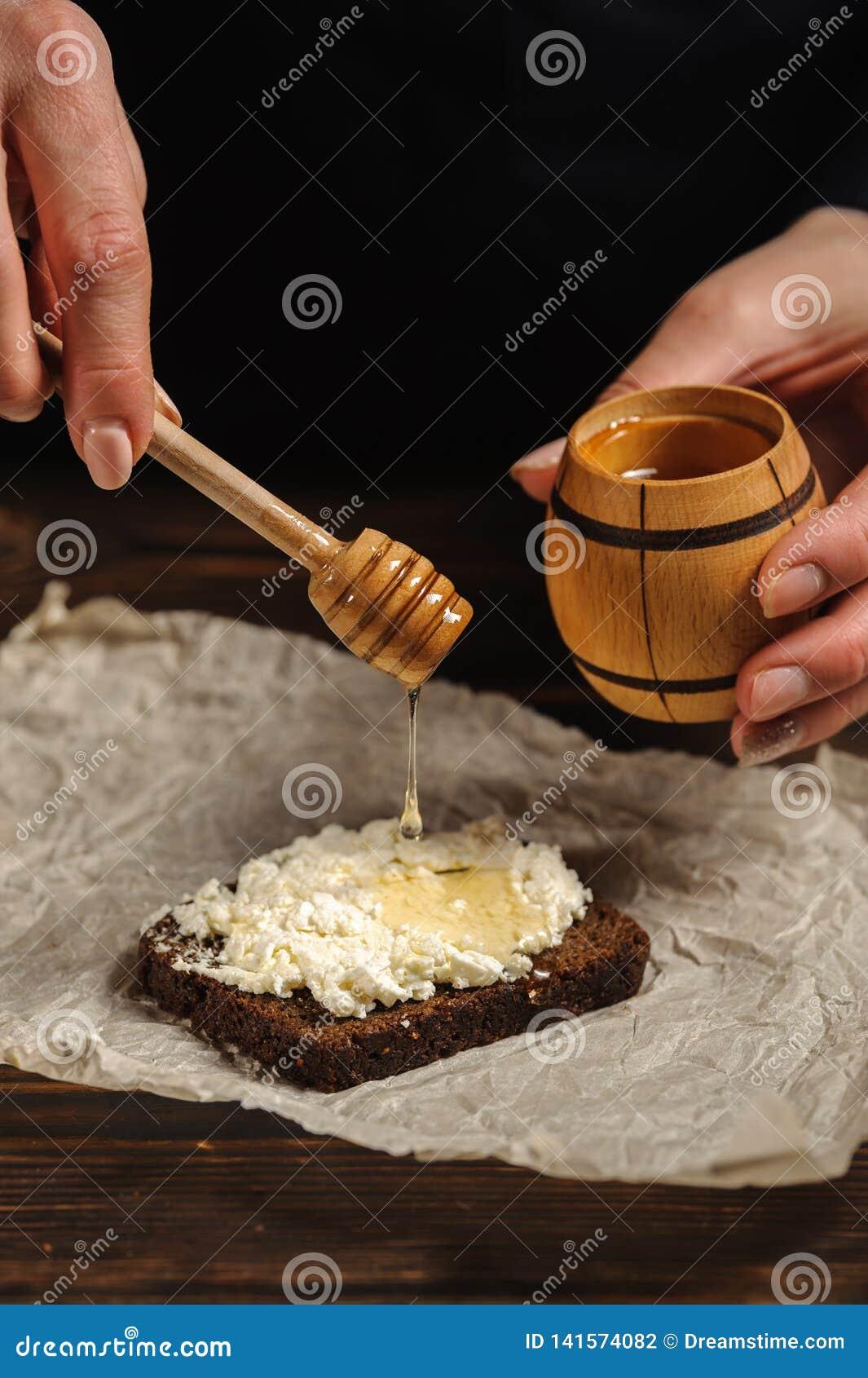 O cozinheiro derrama o mel no pão
