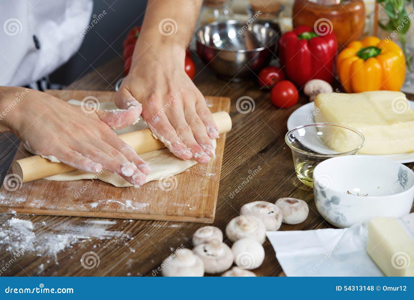 O cozinheiro prepara a massa da pizza