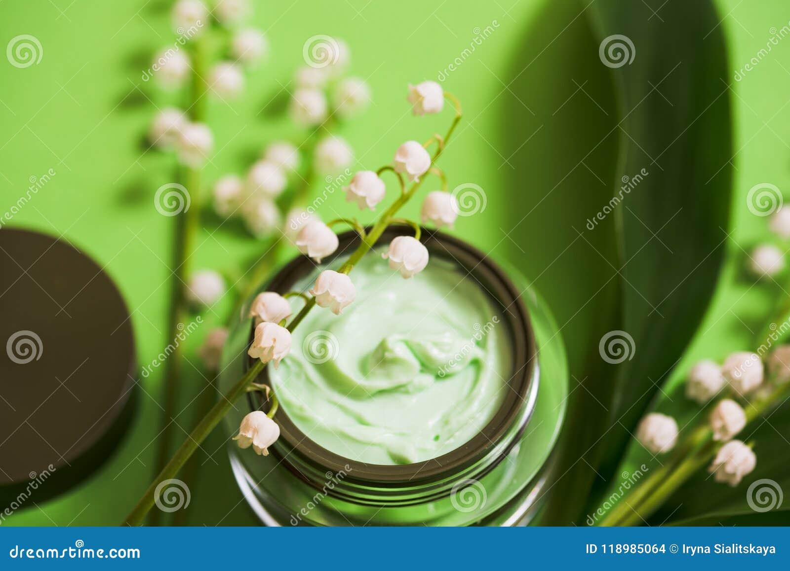 O creme e o lírio cosméticos do vale florescem em um fundo verde