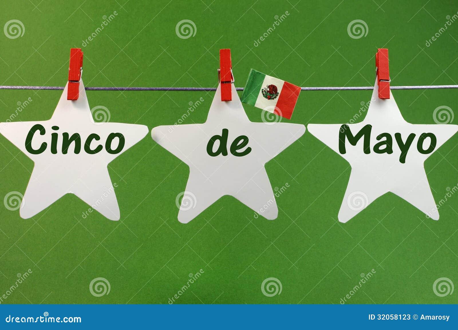 O cumprimento da mensagem de Cinco de Mayo escrito através das estrelas brancas e México embandeiram Pegs de suspensão em uma linh