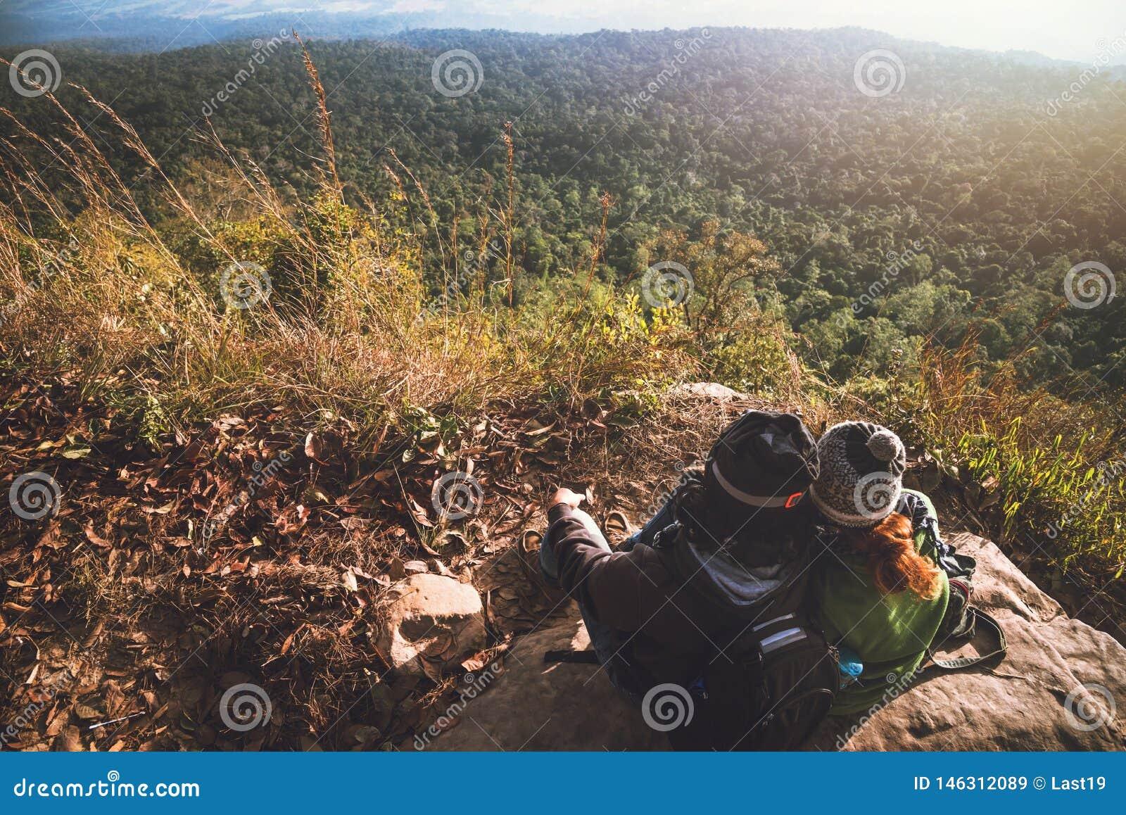 O curso dos asi?ticos das mulheres e dos homens do amante relaxa no feriado Admire a paisagem da atmosfera na montanha Parque da