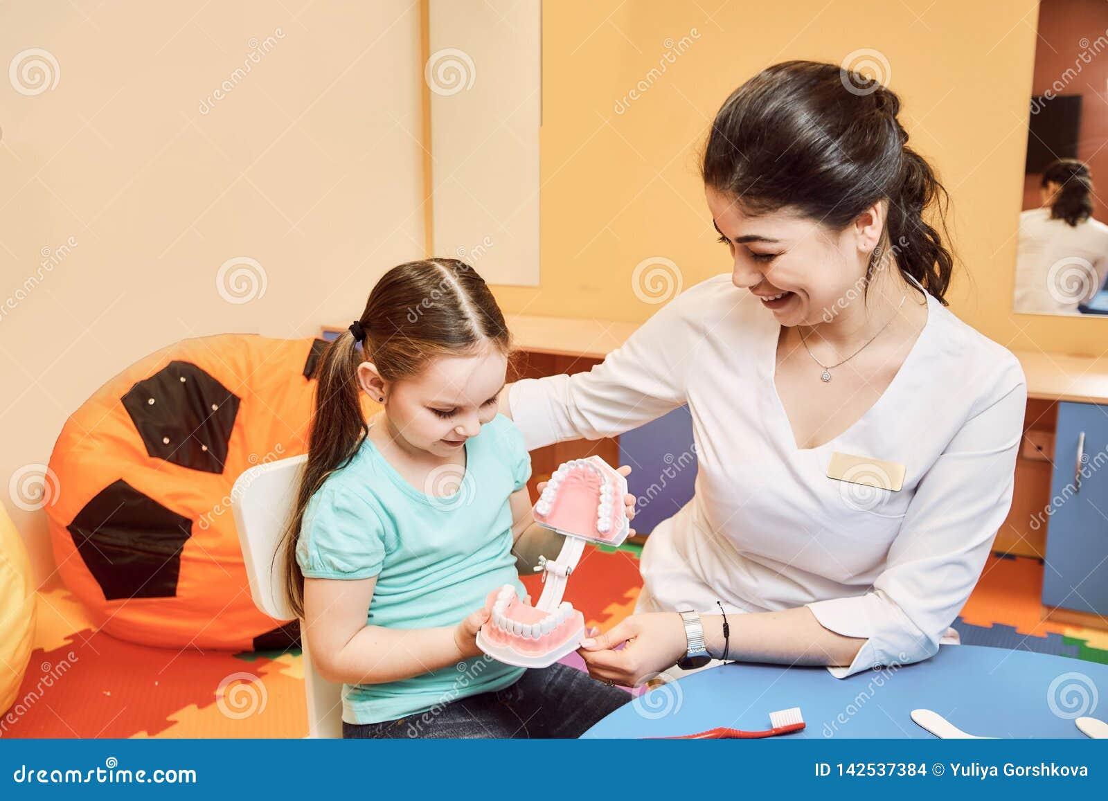 O dentista da mulher ensina a menina escovar seus dentes