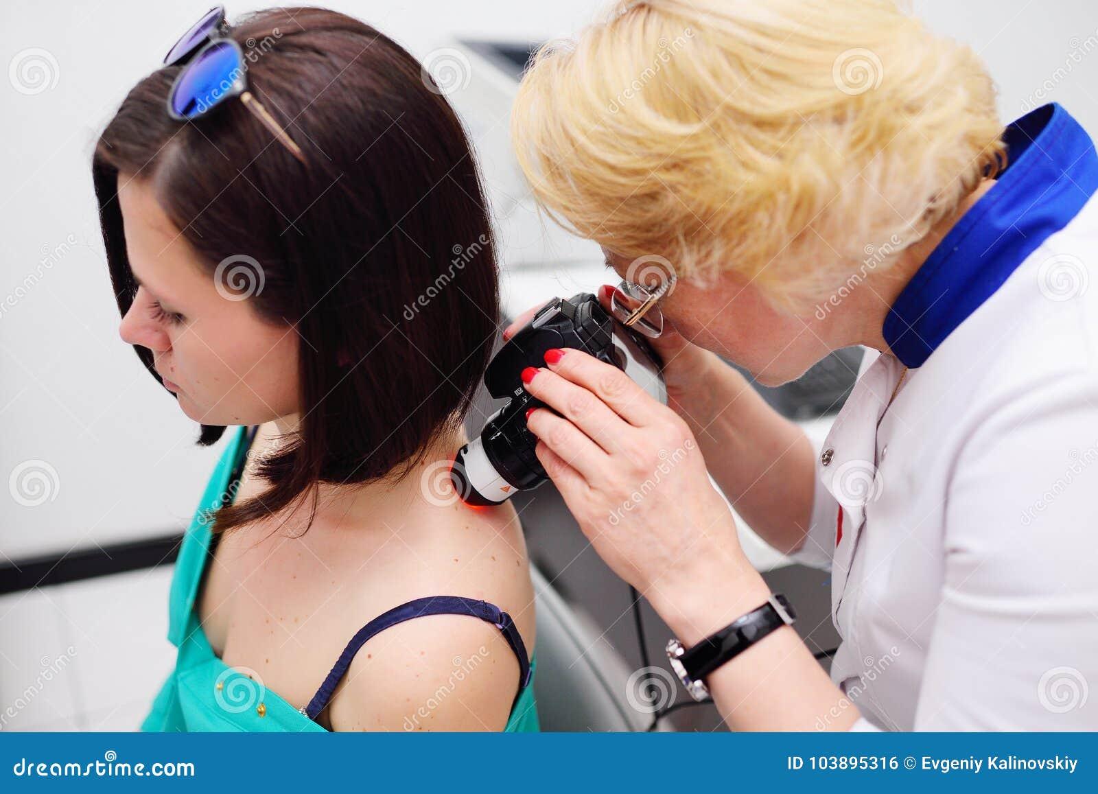 O dermatologista examina as toupeiras ou a acne do paciente com um dermatoscope