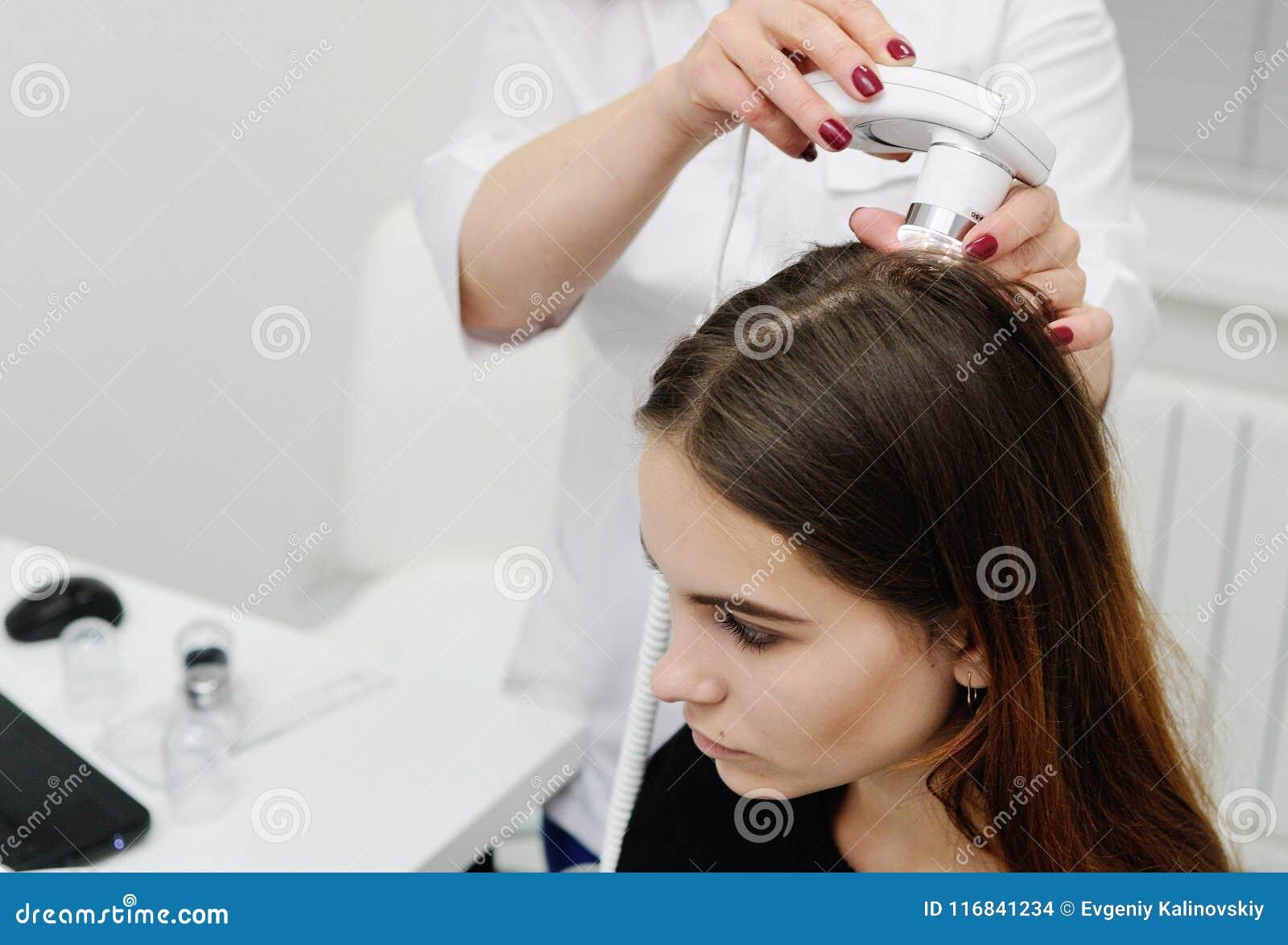O dermatologista examina um cabelo paciente da mulher usando um dispositivo especial