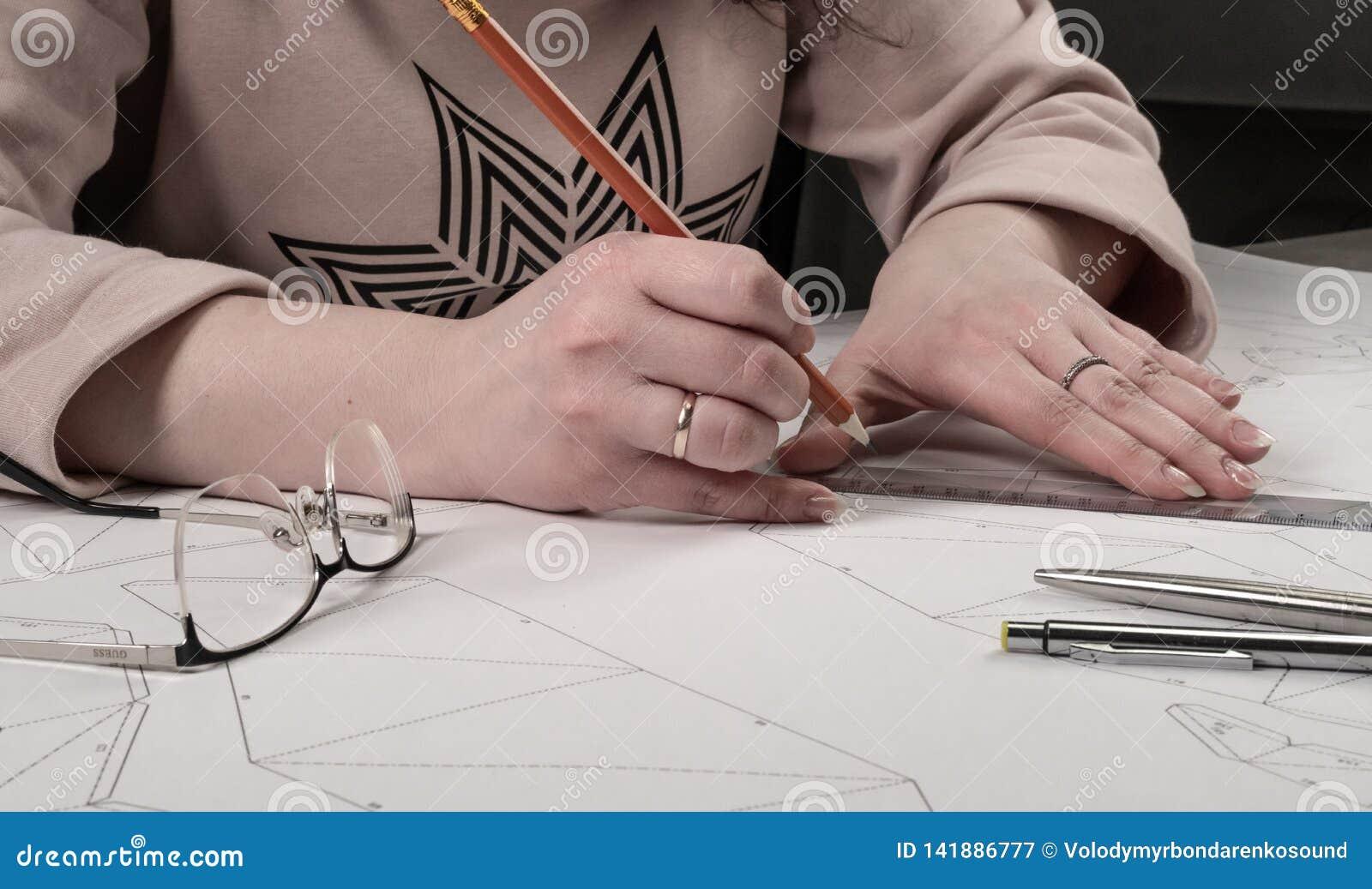 O desenhista fêmea faz um desenho de trabalho Local de trabalho de um desenhista do brinquedo Os marcadores, a régua, a pena e o