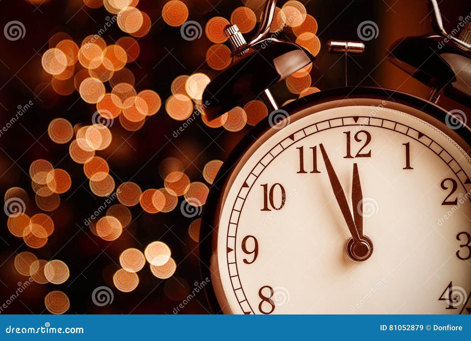 O despertador do vintage está mostrando o meio-dia ou a meia-noite É pulso de disparo do ` de doze o, Natal e bokeh, conce festiv
