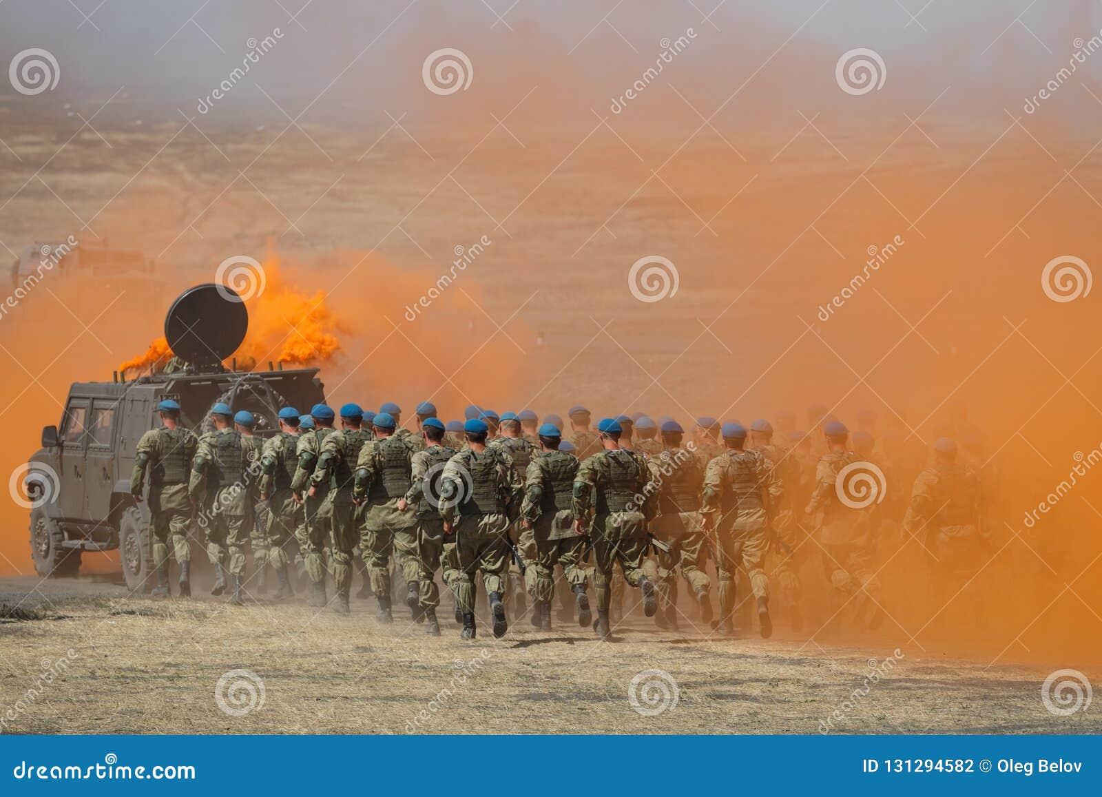 O destacamento de paramilitares do russo corre para um carro blindado através do campo no fumo alaranjado protetor