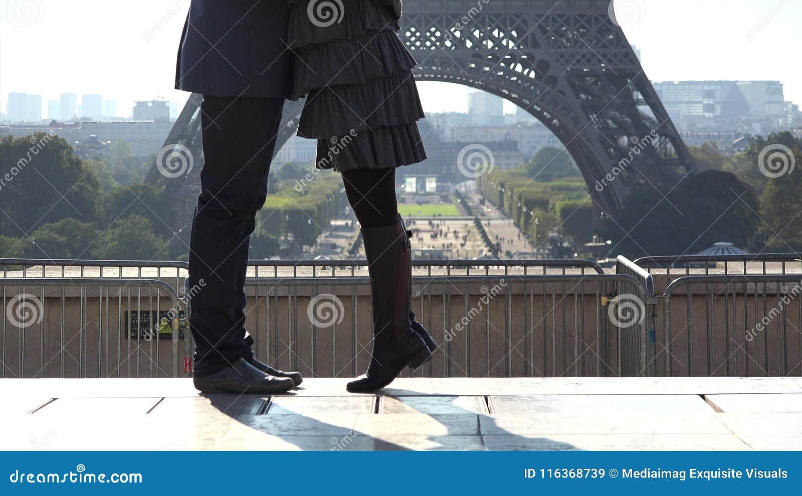 O detalhe de pares de pés dos amantes que datam a torre Eiffel próxima, o homem e a mulher amam vídeos de arquivo