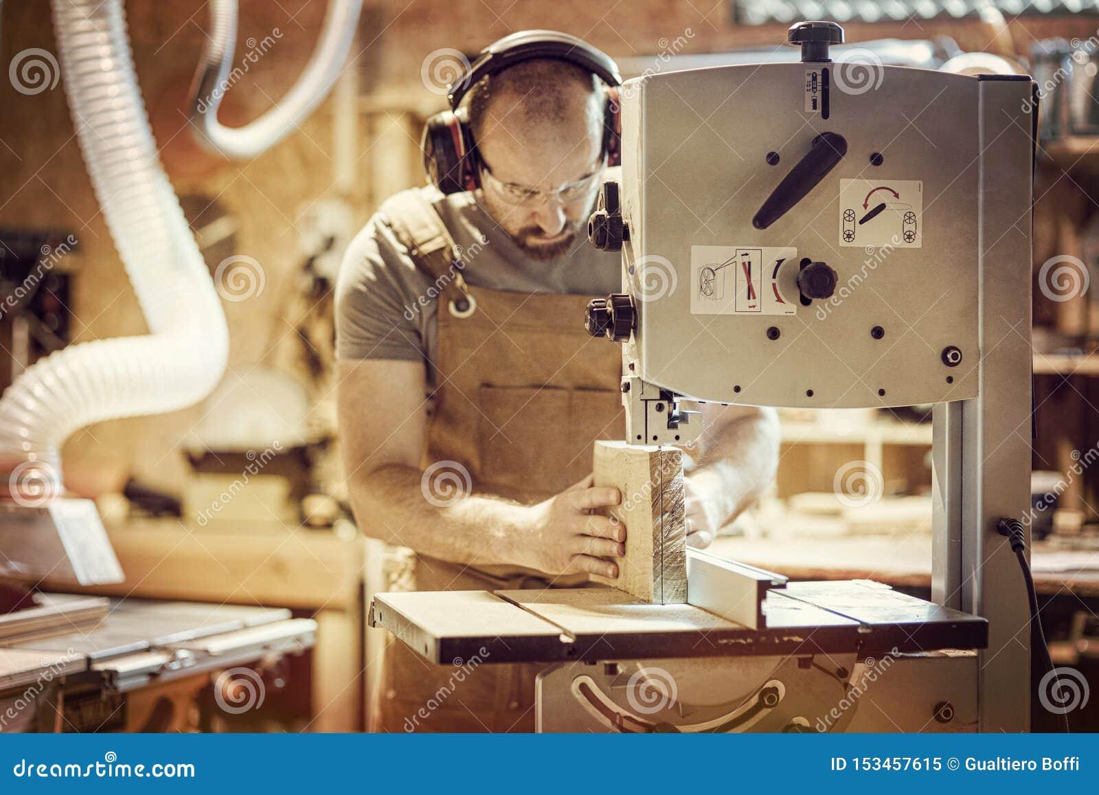 O detalhe de um carpinteiro no trabalho que corta uma prancha com uma faixa considerou em sua oficina