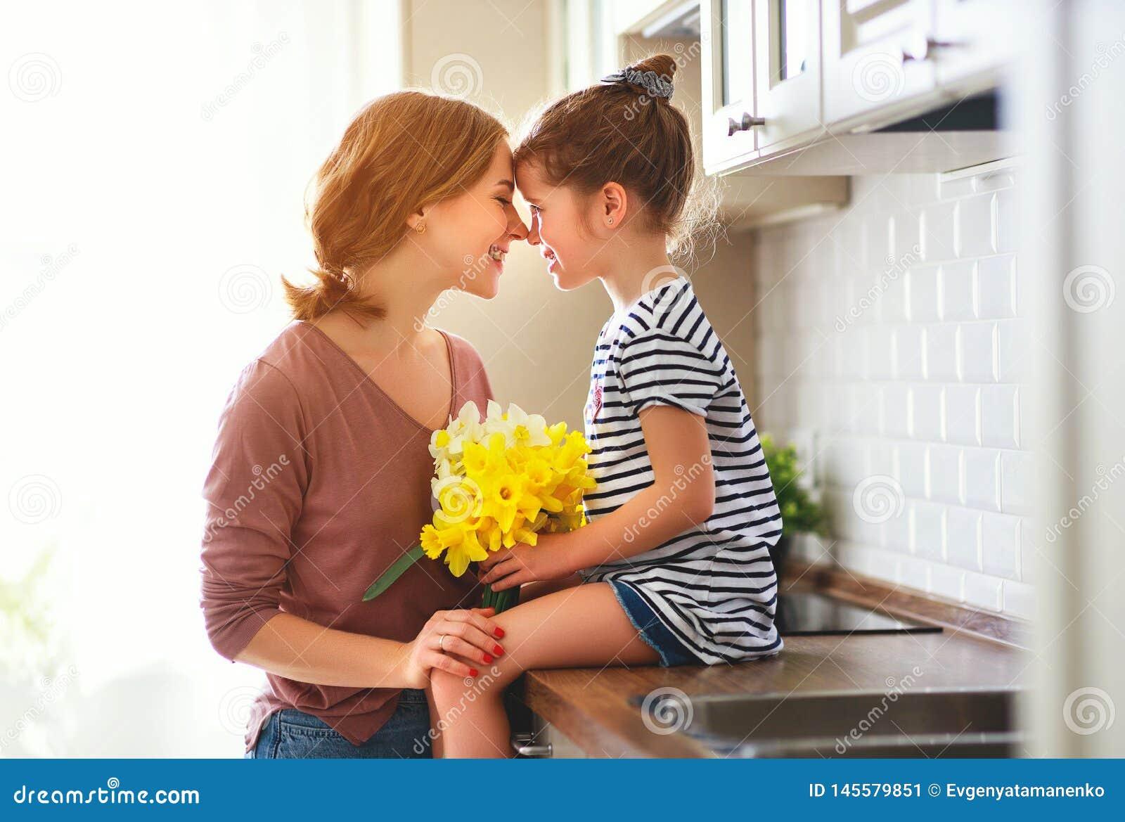 O dia de m?e feliz! a filha da crian?a d? a m?e um ramalhete das flores aos narciso e ao presente