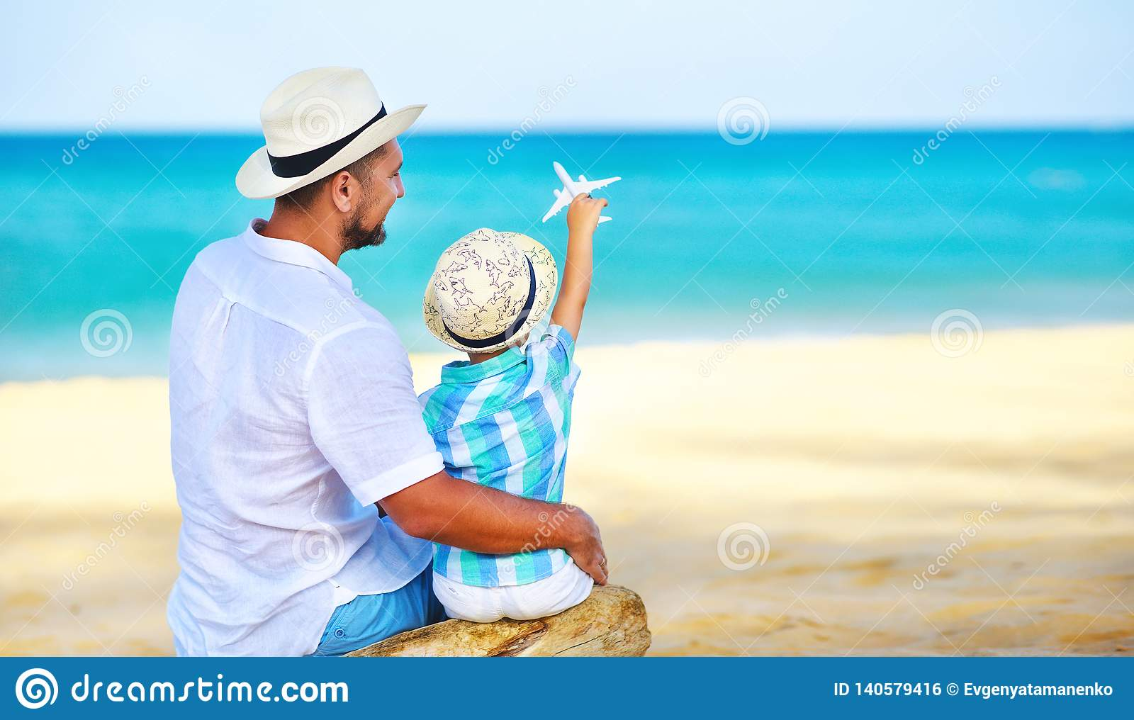 O dia de pai feliz! filho do paizinho e da criança na praia pelo mar com plano modelo do brinquedo