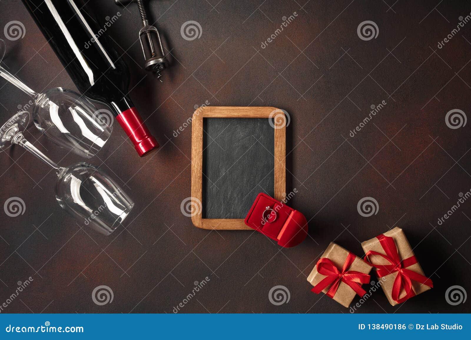 O dia de Valentim com corações, vinho, vidros, presentes, uma caixa sob a forma de um coração e um corkscrew