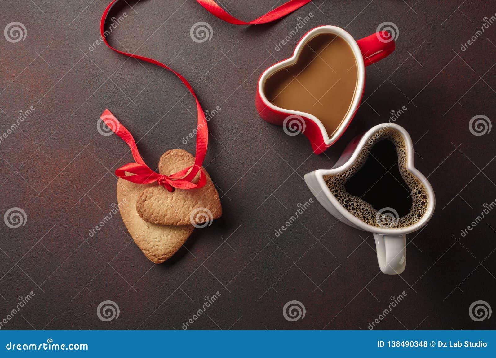 O dia de Valentim com presentes, uma caixa coração-dada forma, umas xícaras de café, as cookies coração-dadas forma, os bolinhos