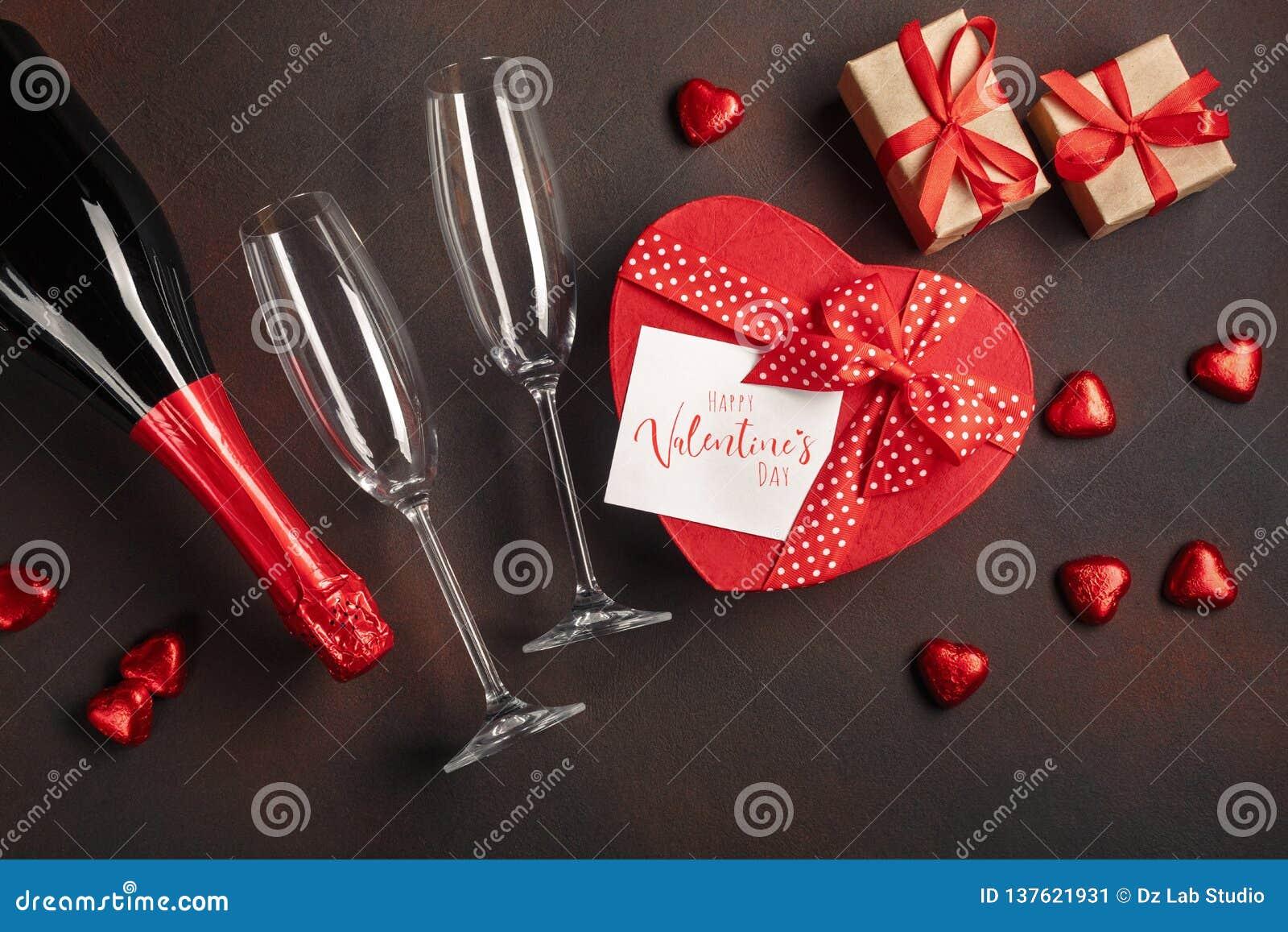 O dia de Valentim com uma garrafa de vidros do champanhe dos chocolates e dos presentes Vista superior com espaço da cópia