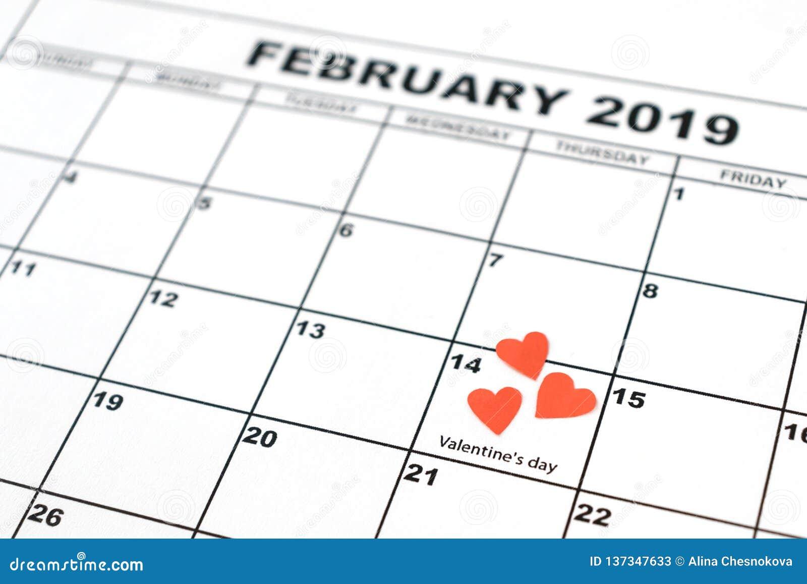 O dia de Valentim, o 14 de fevereiro no calendário com coração vermelho