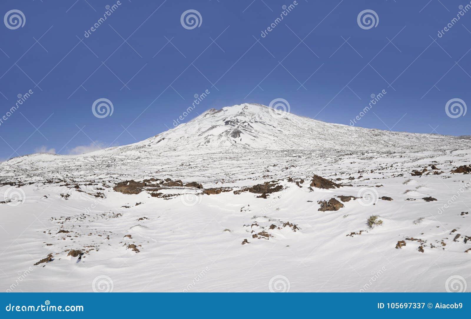O dia ensolarado com vistas para Pico Viejo cobriu na neve no parque nacional de Teide, Tenerife, Ilhas Canárias, Espanha