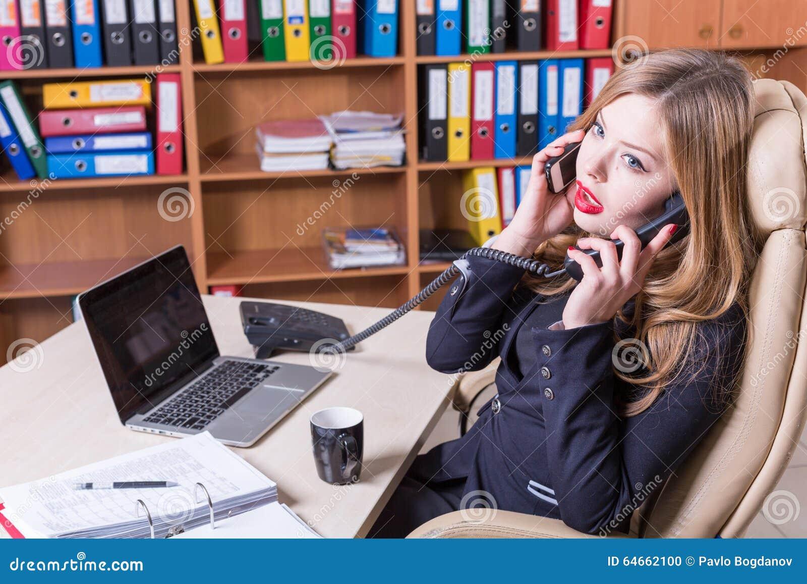 O dia ocupado na mulher do escritório fala em dois telefones