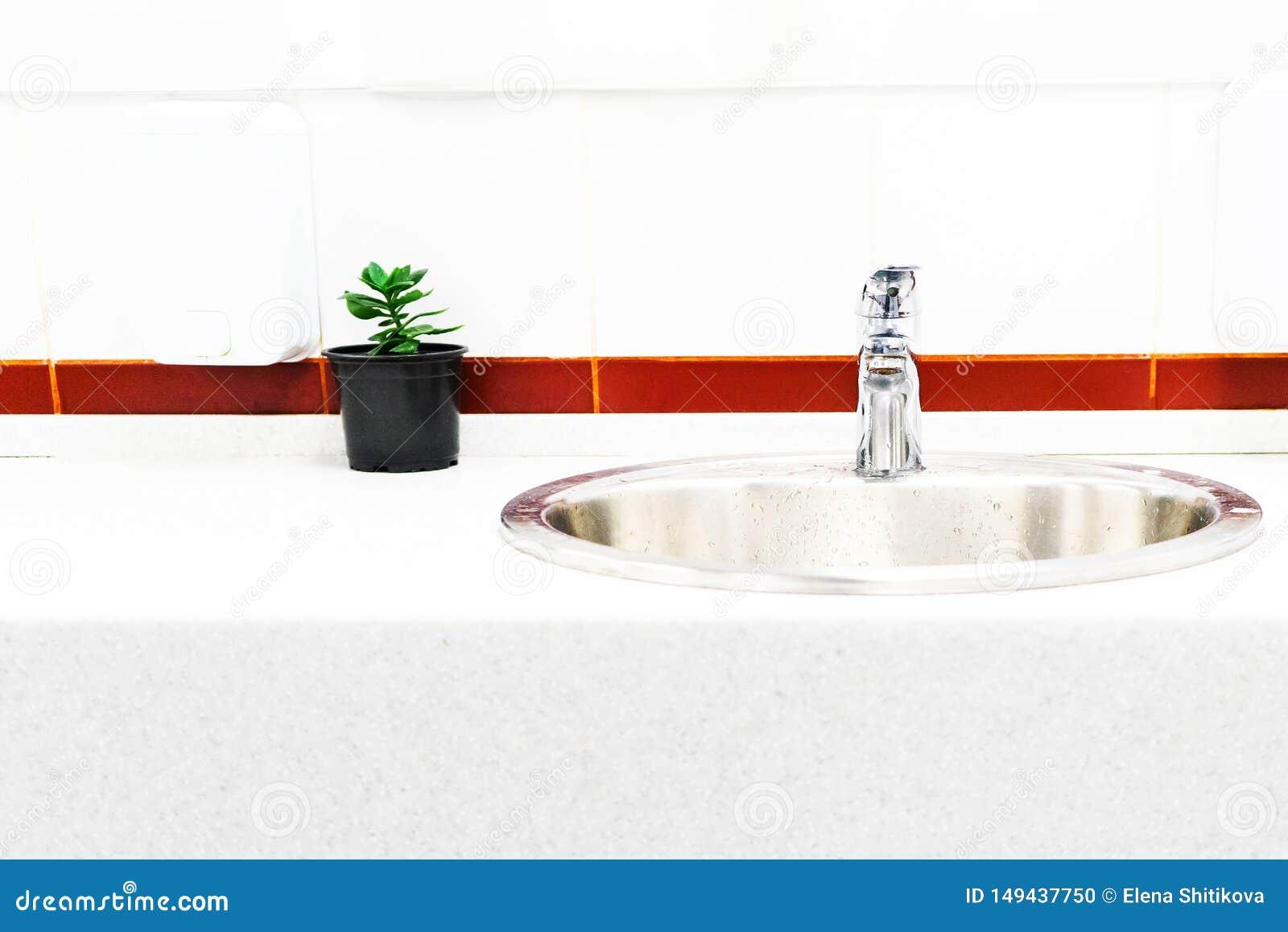 O dissipador no banheiro no fundo de telhas brilhantes com uma listra brilhante, o projeto de uma flor em um potenciômetro