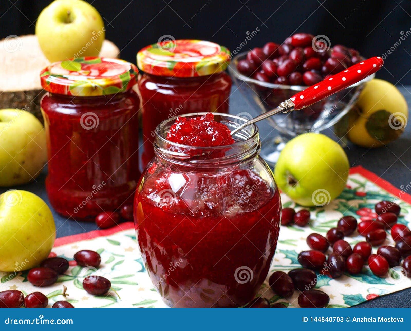 O doce caseiro dos cornisos e das maçãs é ficado situado nos frascos na tabela, um frasco está aberto