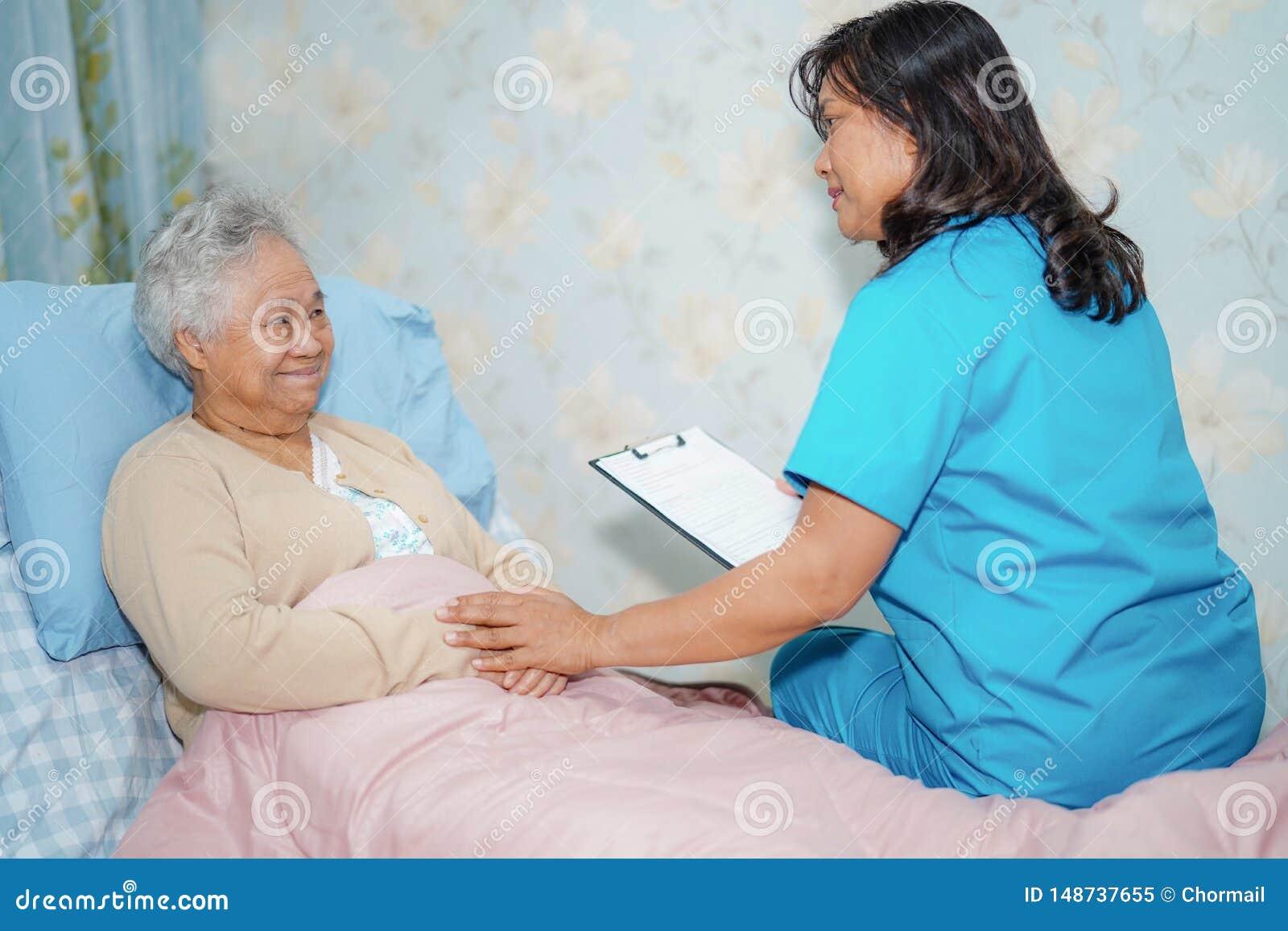 O doutor asi?tico do fisioterapeuta da enfermeira para importar-se, ajudar e apoiar o paciente superior ou idoso da mulher da sen