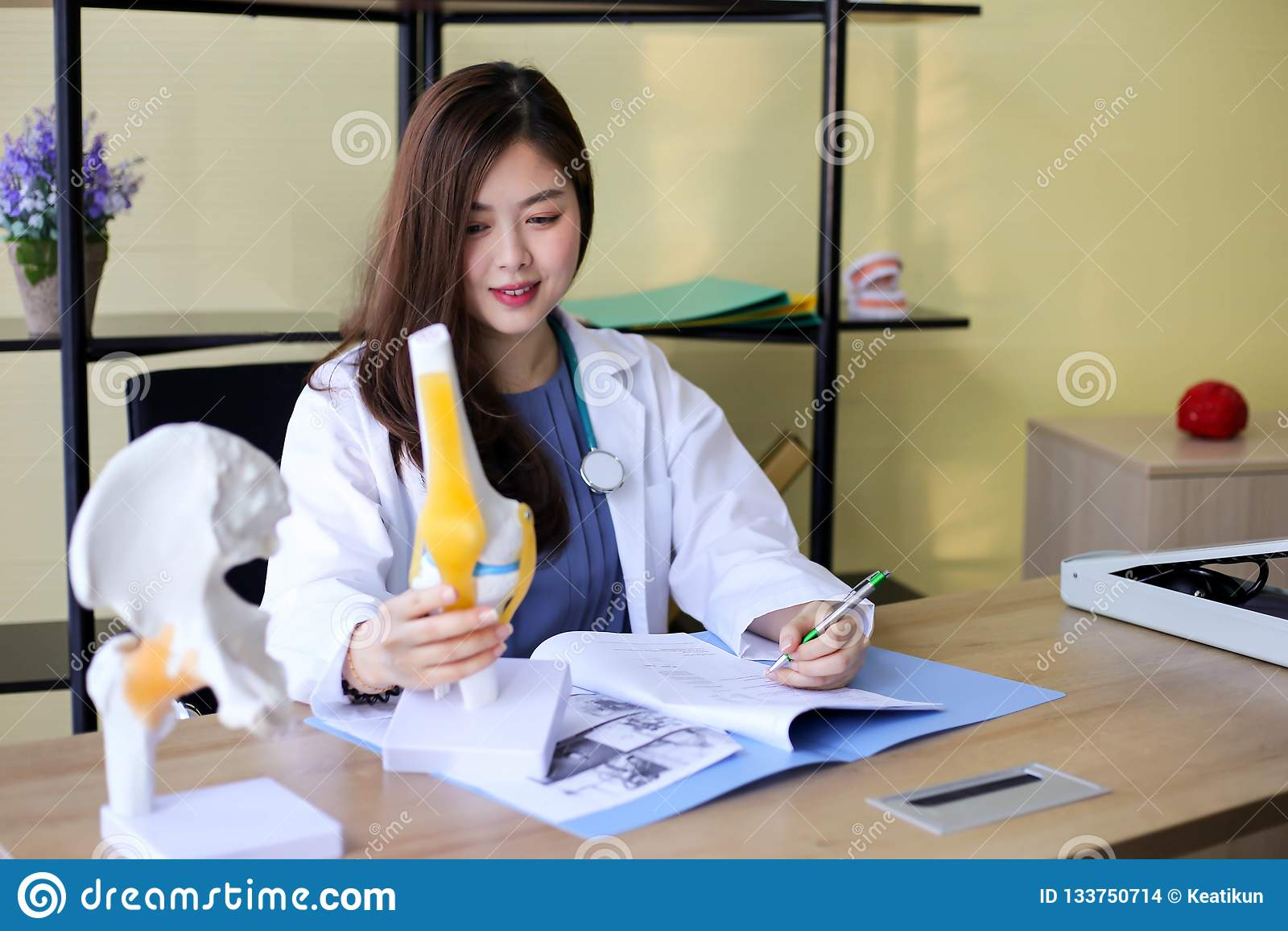 O doutor bonito da mulher está apontando em um osso na espinha o la