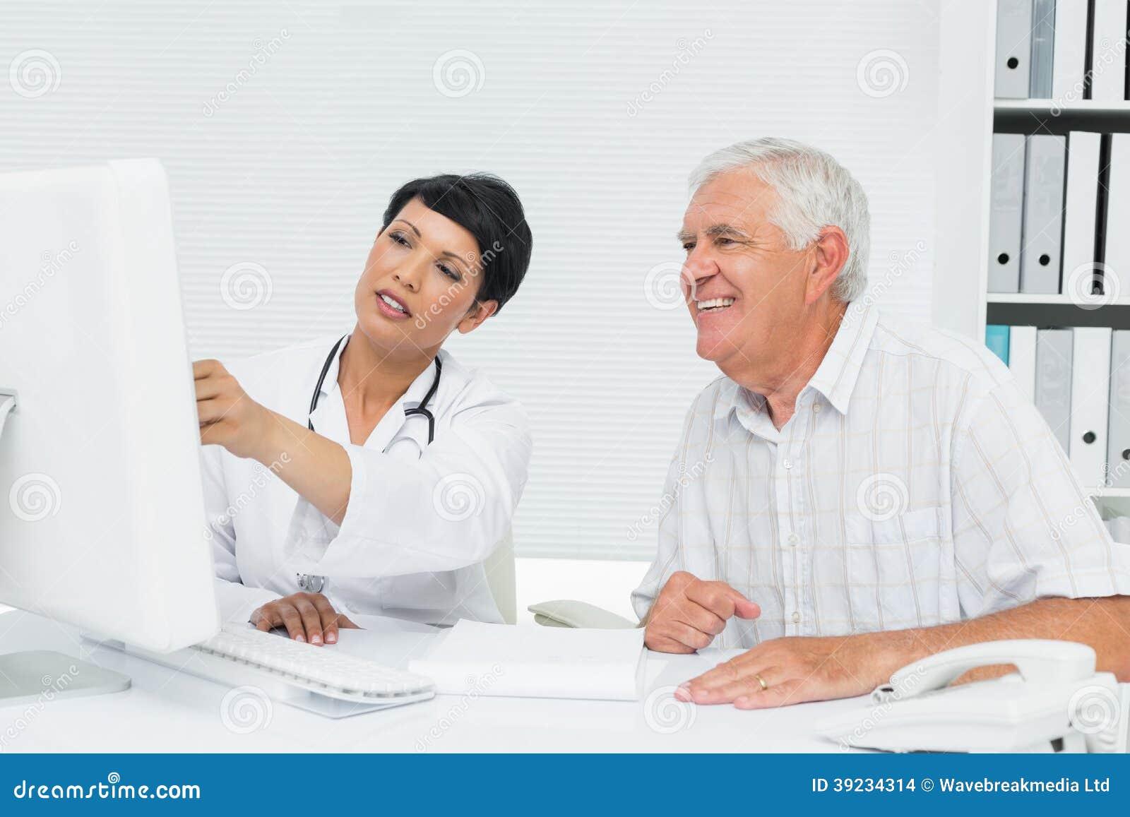 O doutor com leitura paciente masculina relata no computador