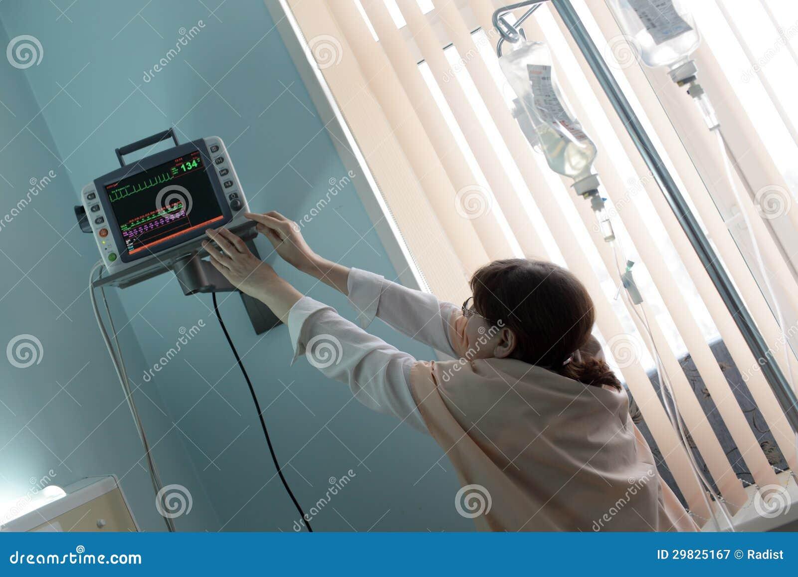 Doutor que ajusta o monitor paciente