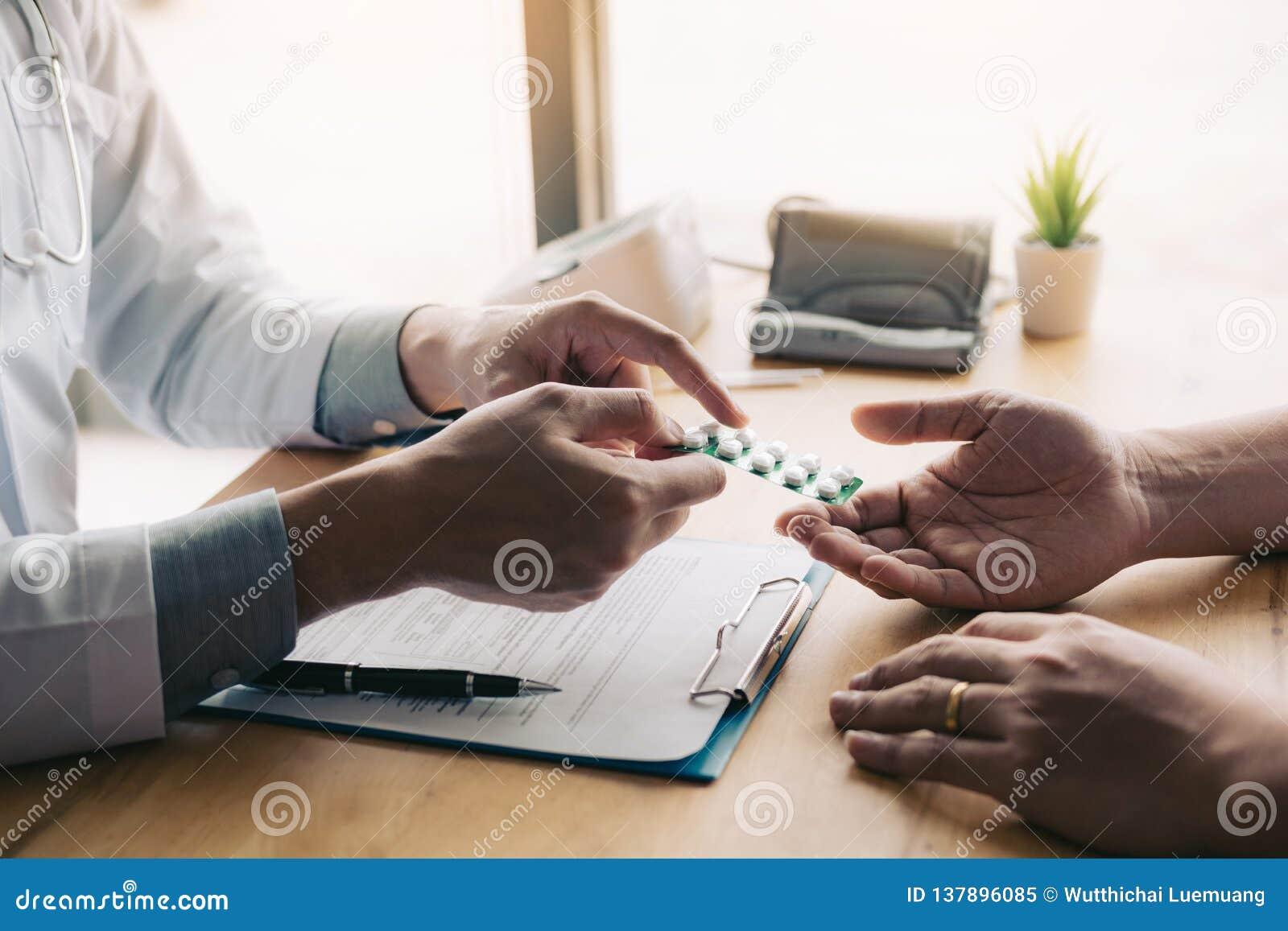 O doutor está apontando para drogar a tabuleta e está introduzindo as propriedades do analgésico ao paciente no escritório