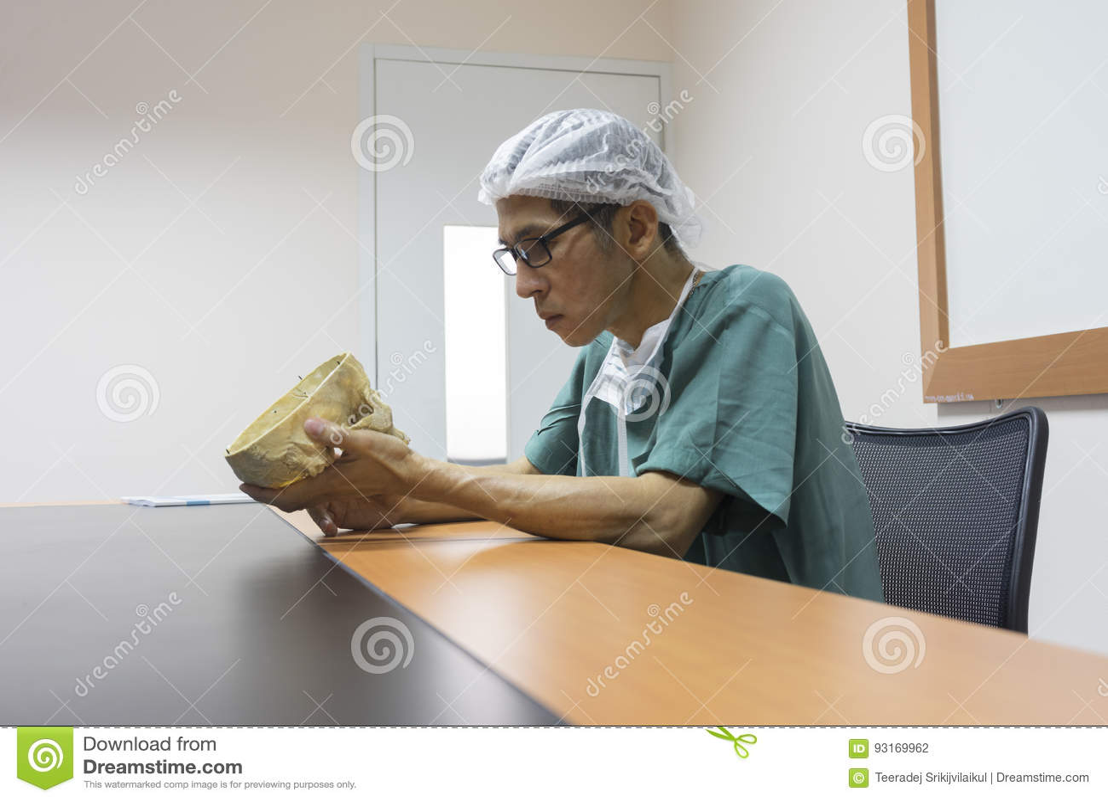 O doutor está estudando o modelo humano do crânio a biblioteca
