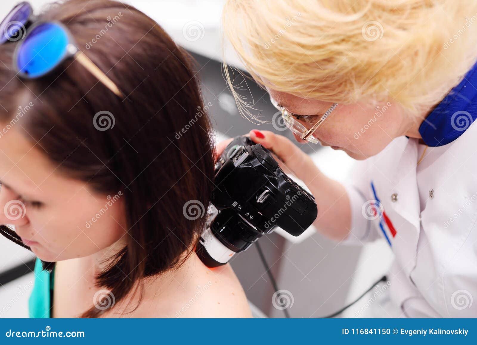 O doutor examina a toupeira paciente do ` s