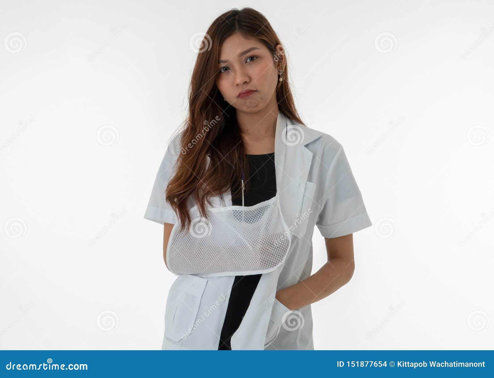 O doutor fêmea mostra uma expressão furada em seu braço quebrado