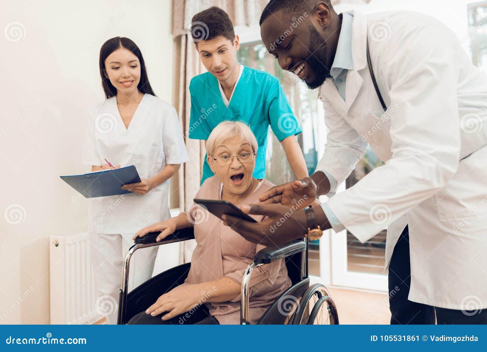 O doutor mostra algo na tabuleta a um paciente idoso em um lar de idosos