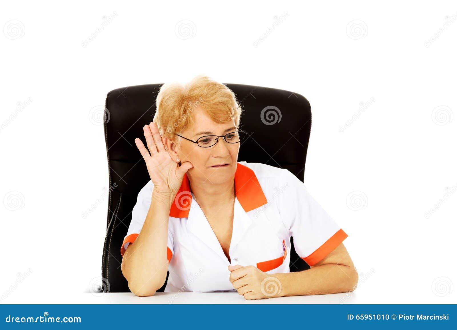 O doutor ou a enfermeira fêmea idosa do sorriso que sentam-se atrás da mesa e bisbilhotam uma conversação