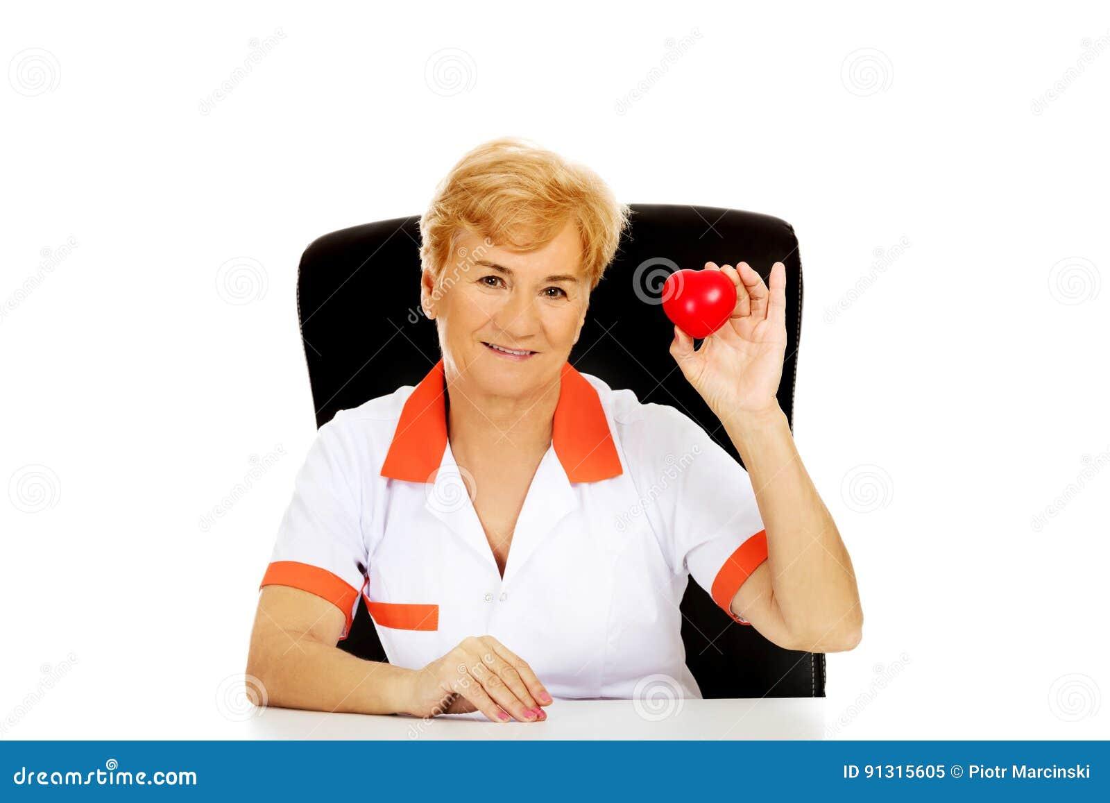 O doutor ou a enfermeira fêmea idosa do sorriso que sentam-se atrás da mesa e do coração das posses brincam