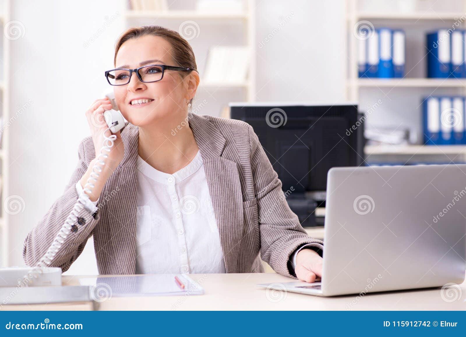 O empregado da mulher de negócios que fala no telefone do escritório