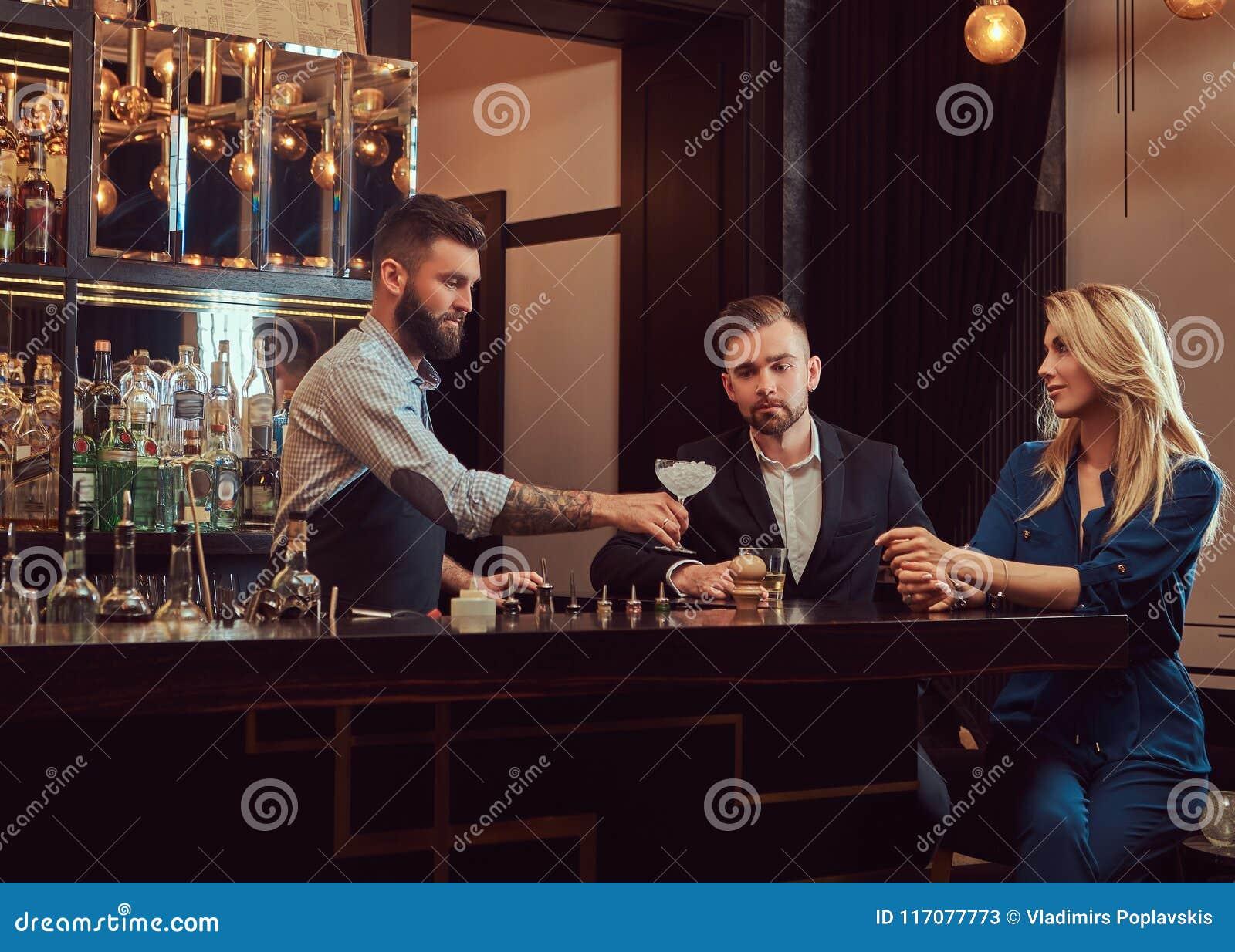 O empregado de bar brutal à moda serve um par atrativo que passe uma noite em uma data