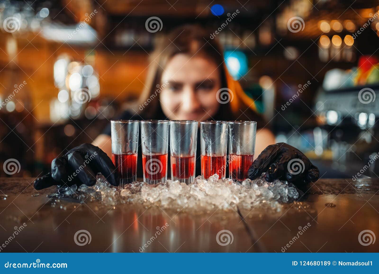 O empregado de bar fêmea nas luvas põe bebidas sobre o gelo
