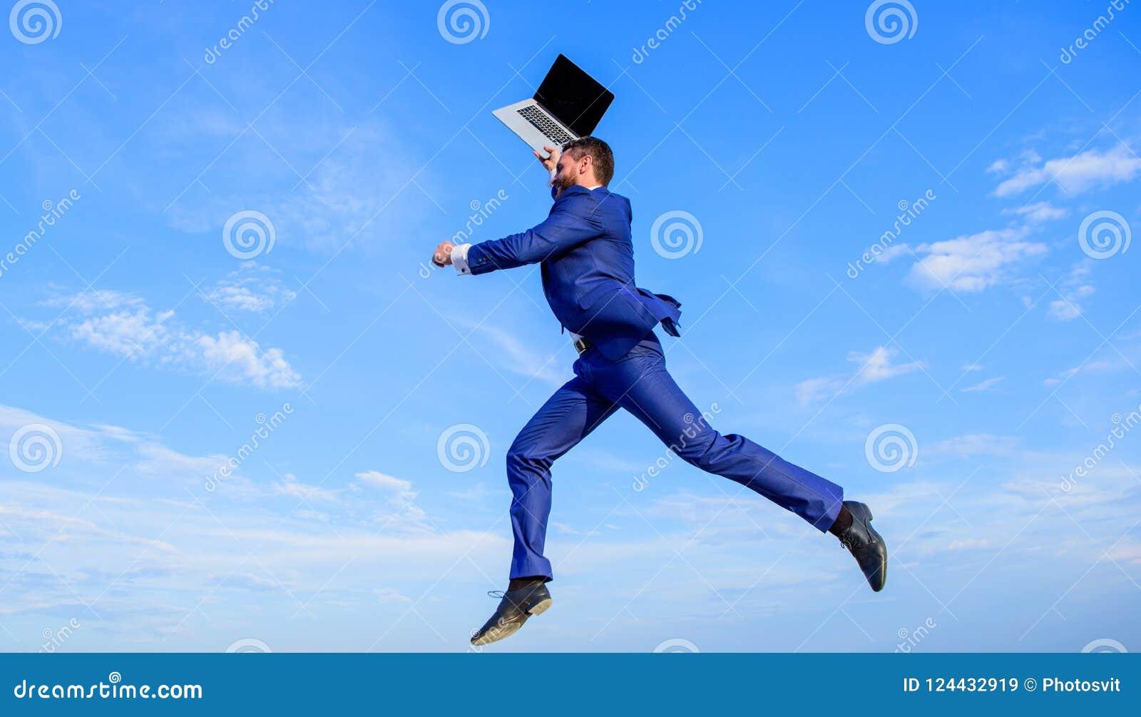 O empresário inspirado homem de negócios sente ir poderoso mudar o mundo O homem inspirado guardar o portátil acima quando salto