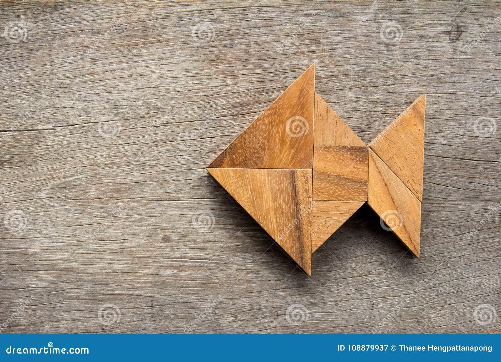 O enigma chinês do tangram nos peixes dá forma no fundo de madeira