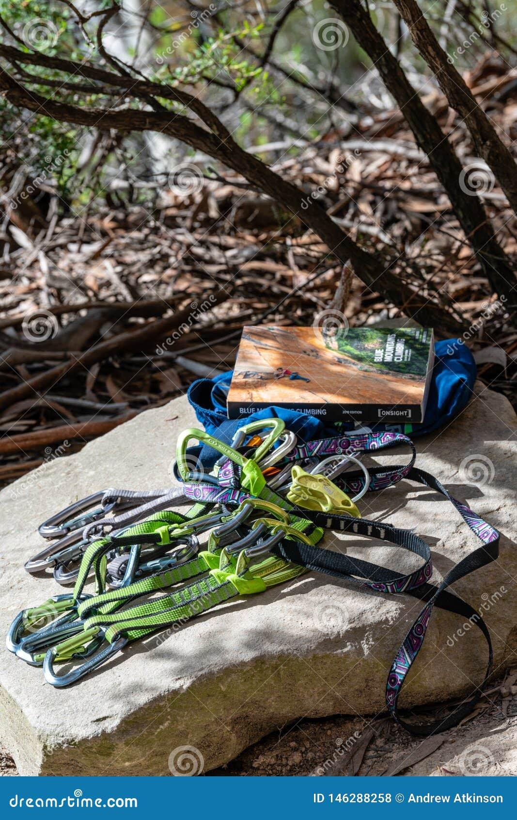 O equipamento da escalada e o guia de escalada apresentaram em uma rocha em paredes Ledge Blackheath