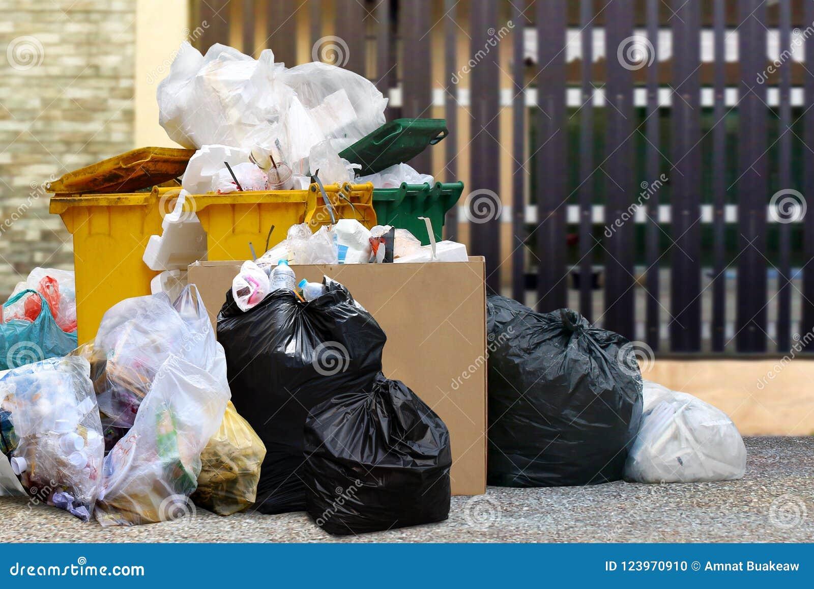 O escaninho waste dos lotes recicla e os sacos de plástico na casa da cerca, muitos do lixo trash a casa dianteira dos sacos de p