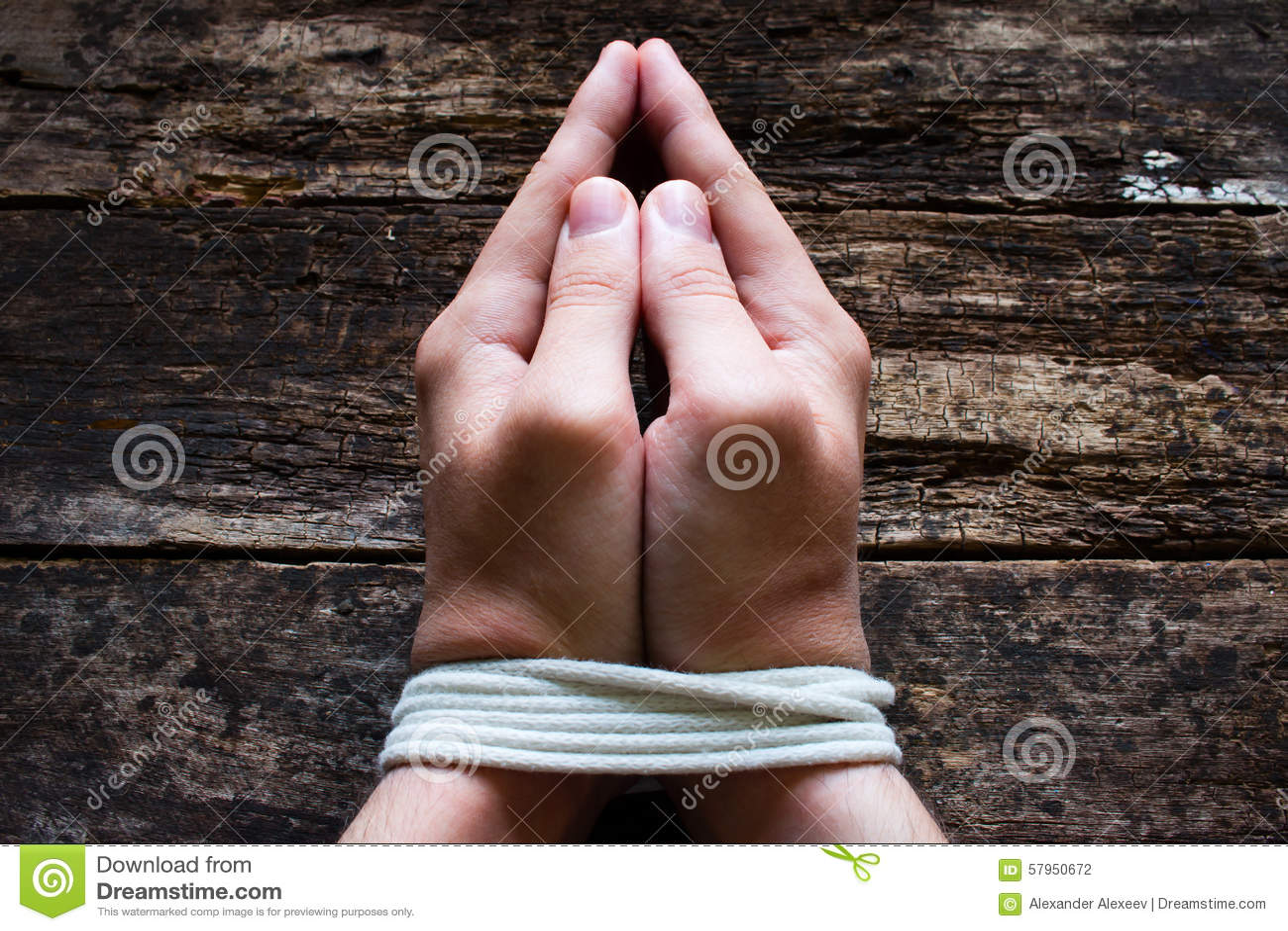 O escravo do homem reza com suas mãos amarradas