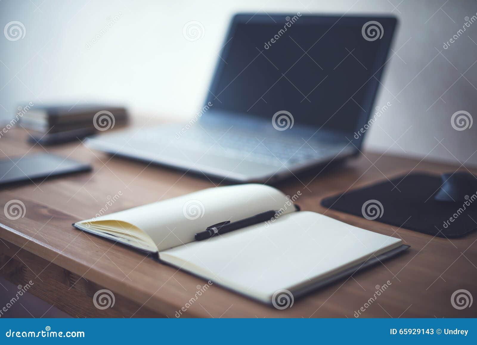 O espaço de trabalho à moda do freelancer com trabalho aberto do bloco de notas do portátil utiliza ferramentas em casa ou local