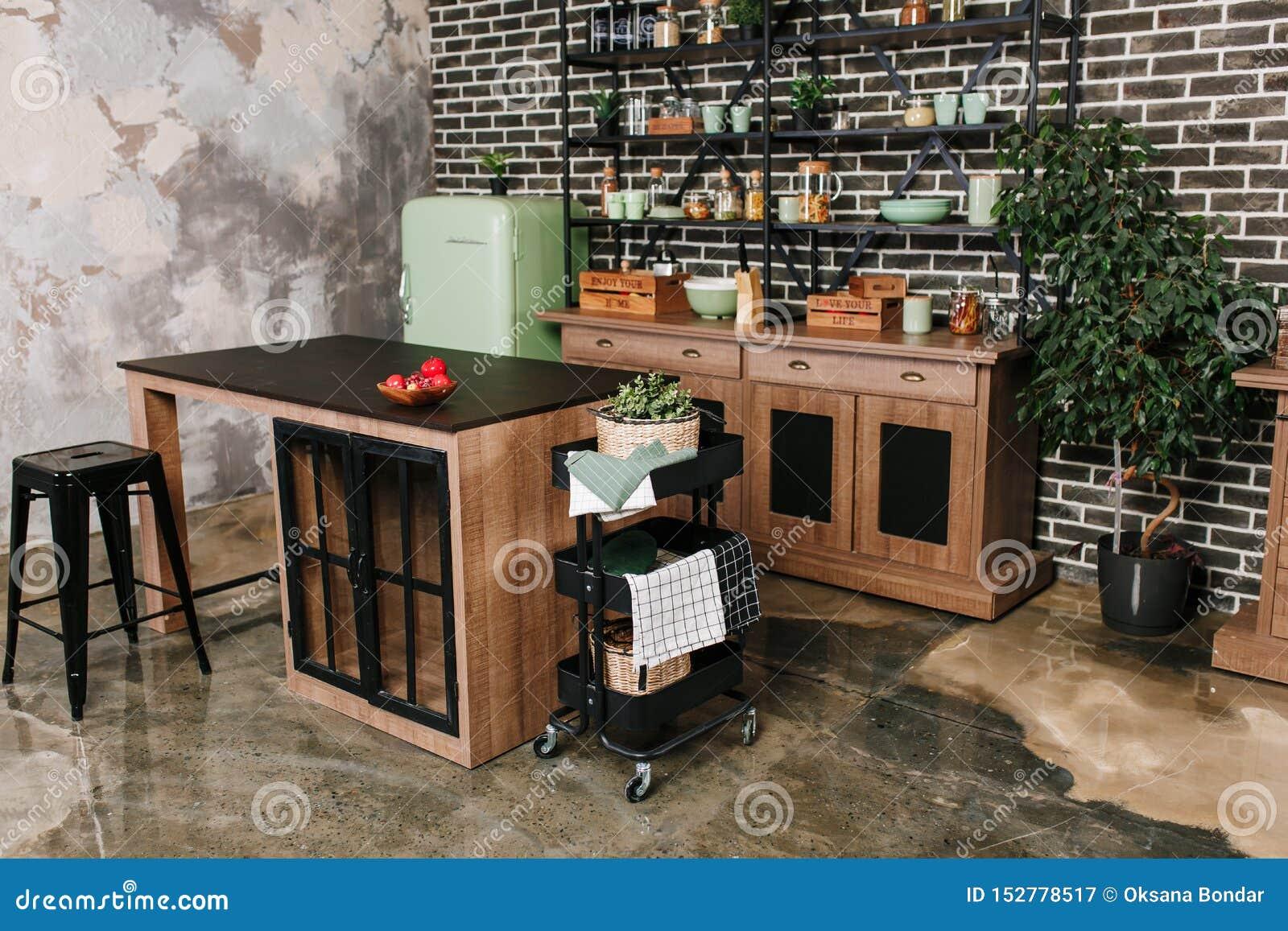 O espaço para refeições no estilo industrial com tabela, cadeiras e refrigerador retro da hortelã Fundo preto da parede de tijolo