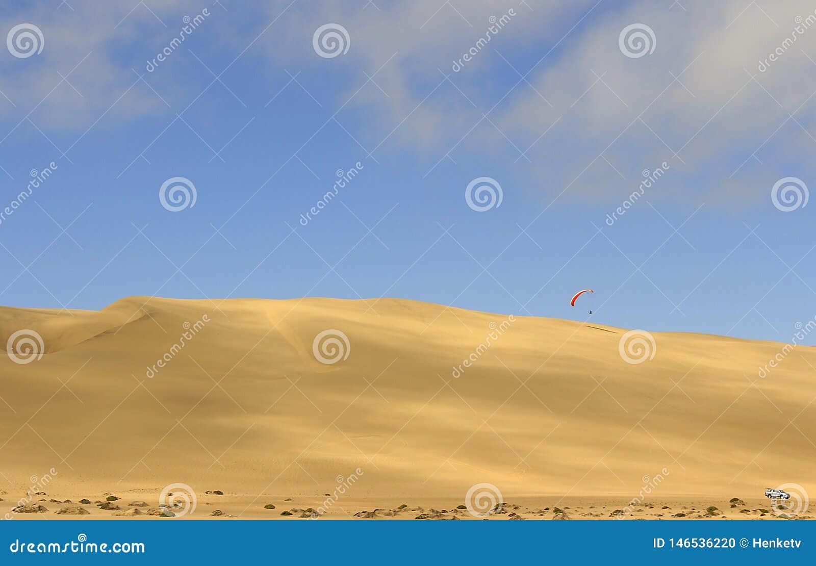 O esporte do salto da duna de areia e de executar manobras acrob?ticas no ar durante a queda livre antes de aterrar pelo paraqued