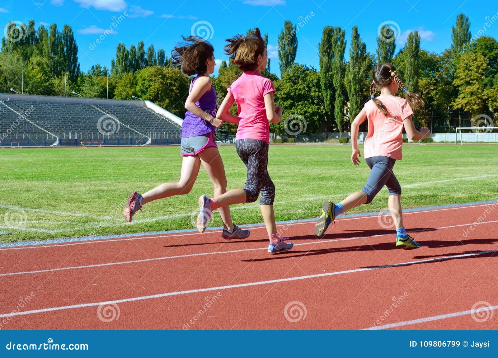 O esporte e a aptidão da família, a mãe feliz e as crianças correndo no estádio seguem fora, conceito saudável do estilo de vida