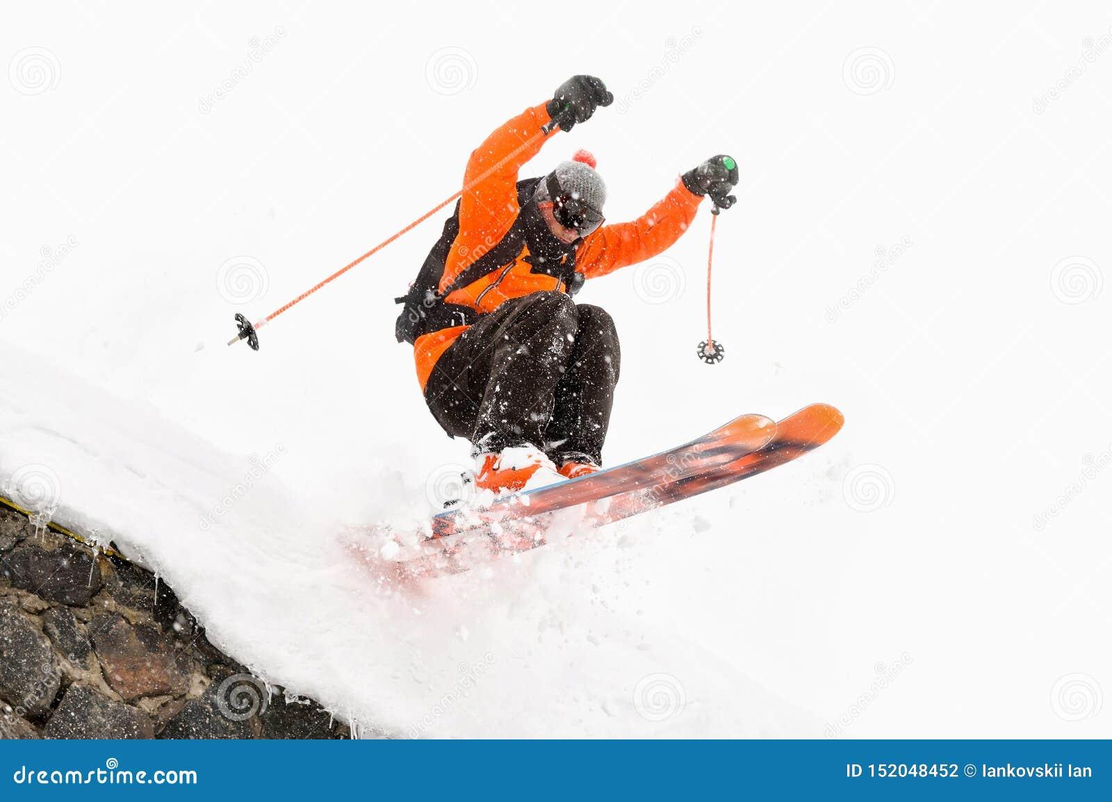 O esquiador do atleta em um fundo claro com um salto move-se fora do telhado de uma cabana coberto de neve com os flocos do voo d
