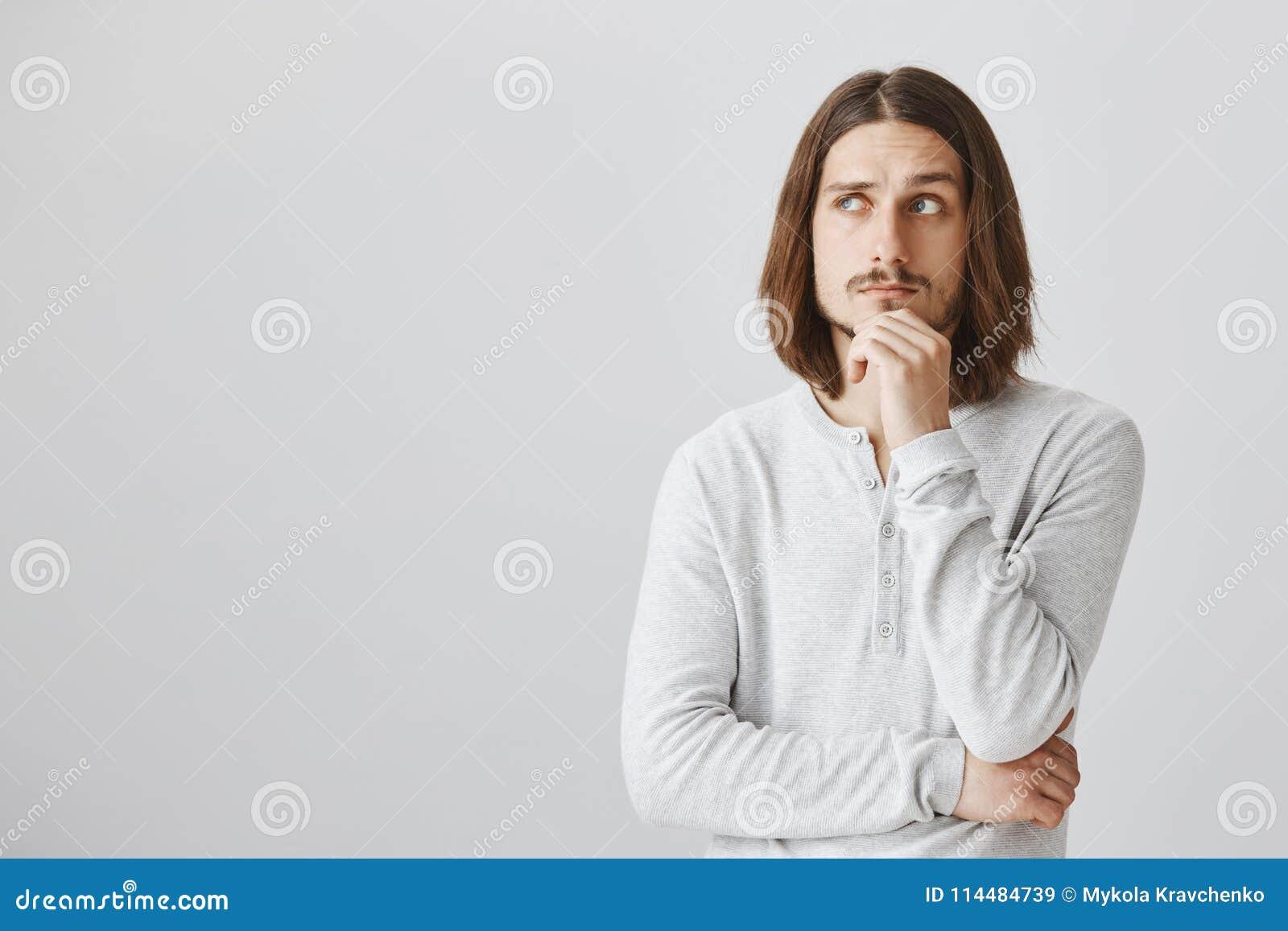 O estúdio disparou do indivíduo esperto considerável com o cabelo justo longo que guarda a mão no queixo e que olha acima, pensan