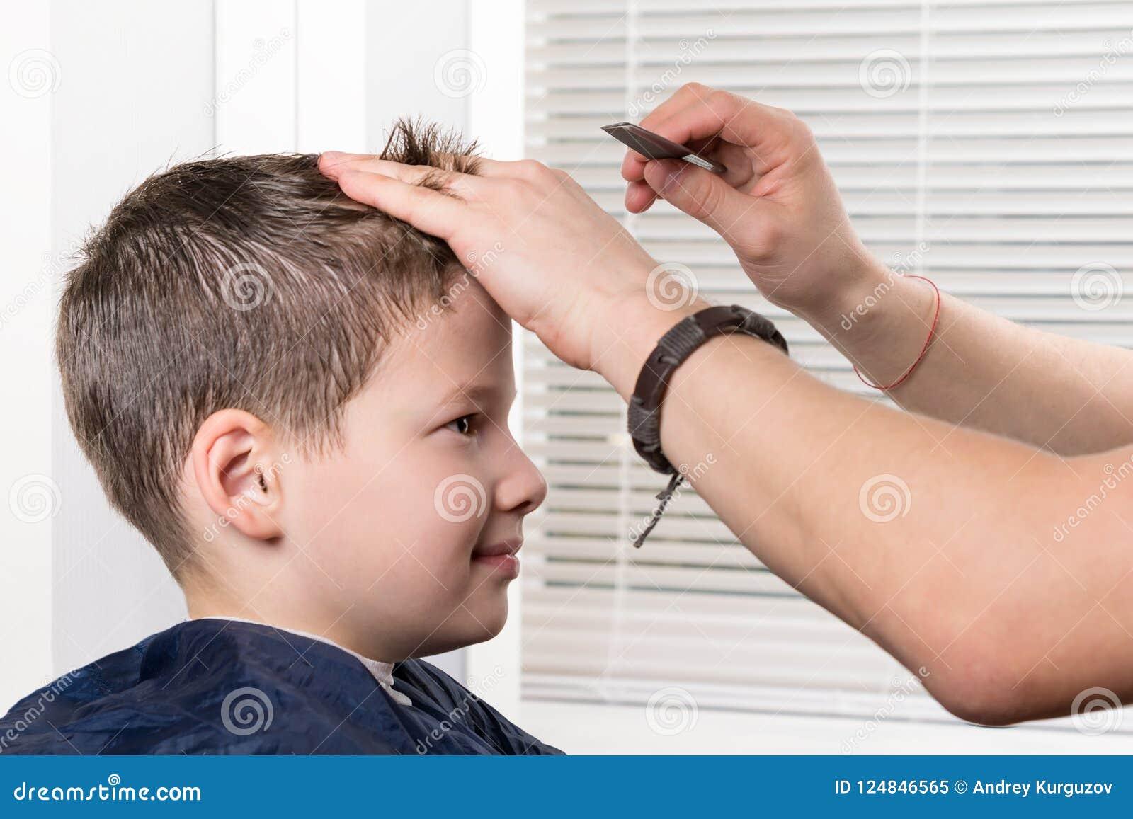O estilista do cabeleireiro faz um penteado para um menino com um pente
