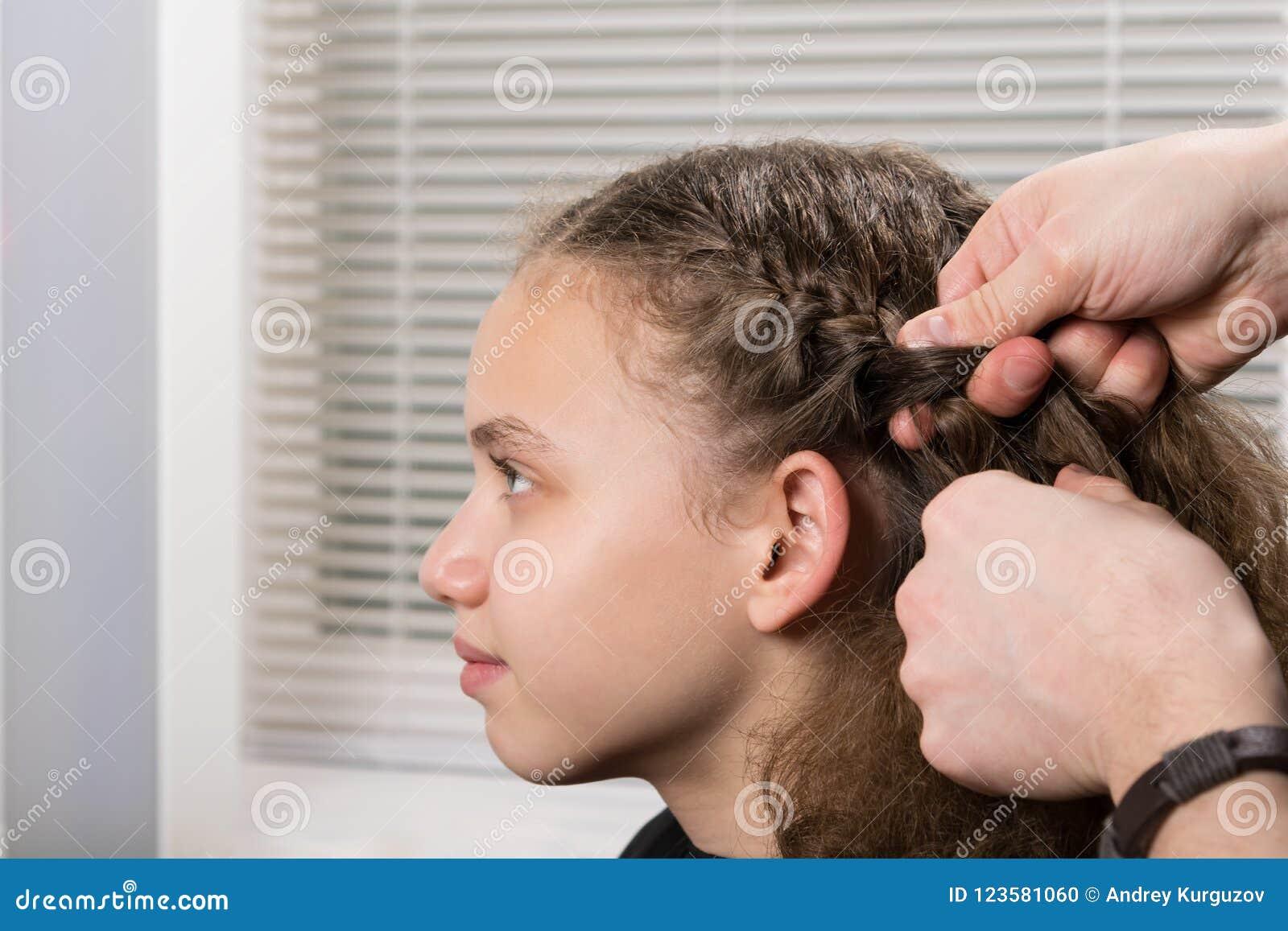 O estilista faz um penteado da menina da trança no salão de beleza
